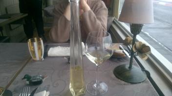 Glaasje wijn gepresenteerd in een glazen flesje.